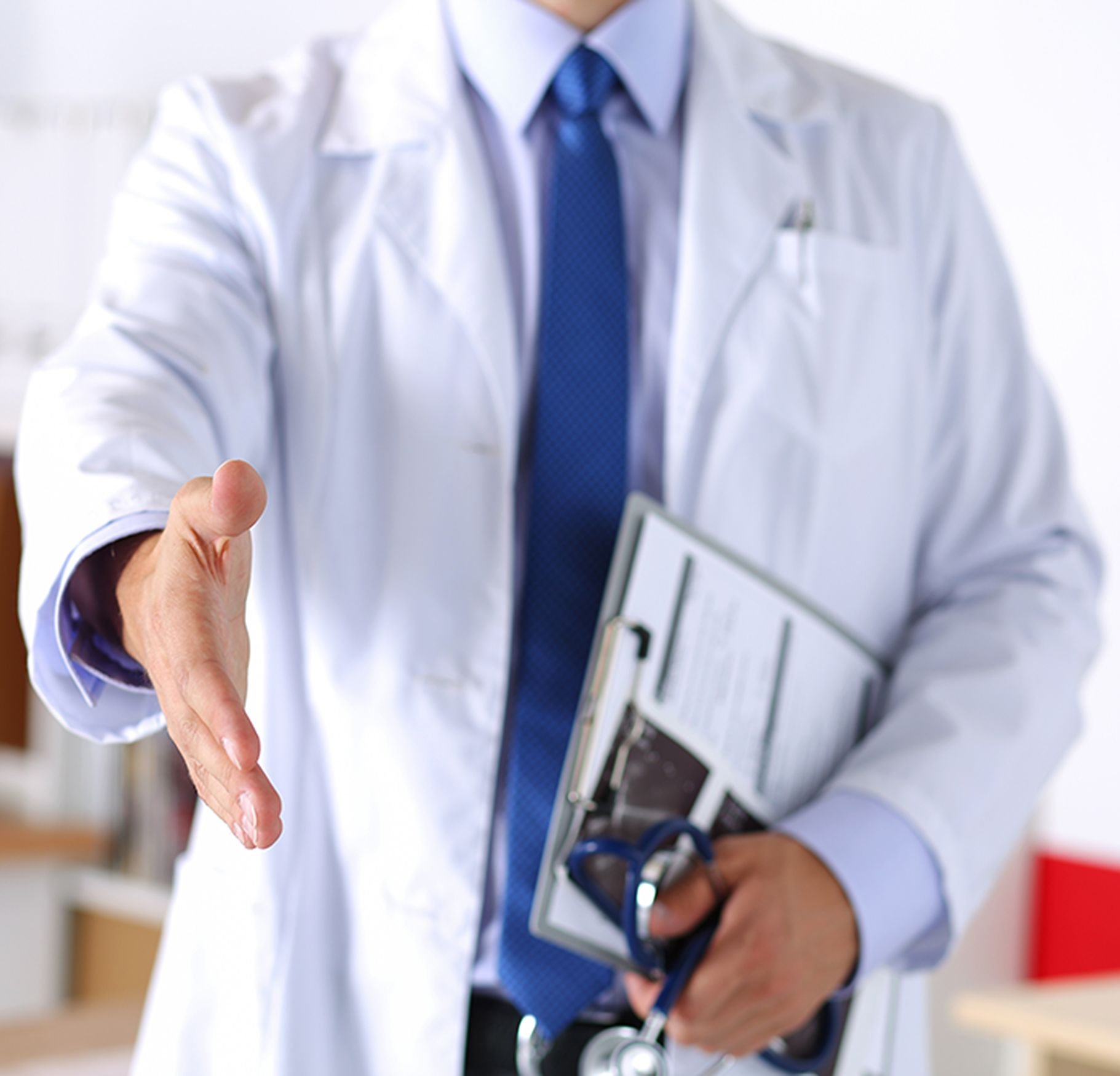 Doctor extending his hand for a handshake with clipboard